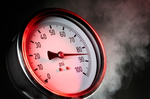 pressure gauge under extreme stress with steam and red warning light